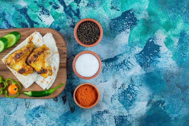 Alas cocidas, lavash y verduras sobre una tabla de cortar, sobre fondo azul.