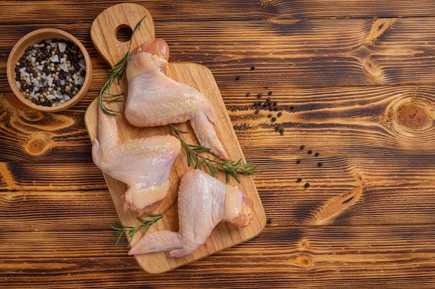 Alas de pollo crudo sobre la superficie de madera oscura.