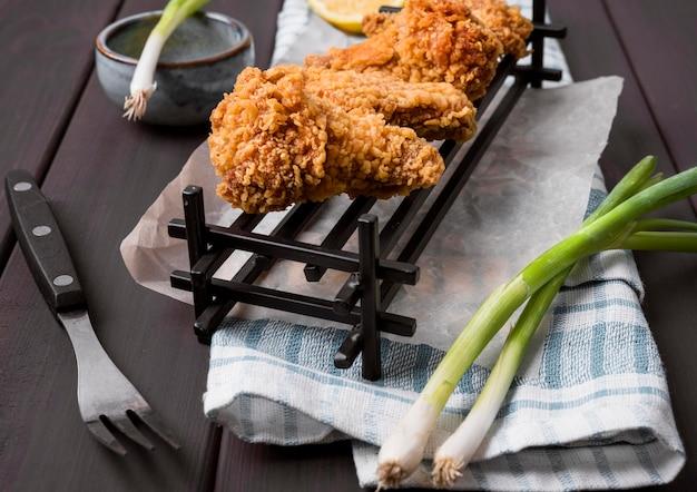 Alas de pollo frito de alto ángulo en bandeja con cebollas verdes y tenedor