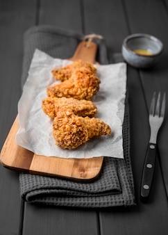Alas de pollo frito de alto ángulo en la tabla de cortar