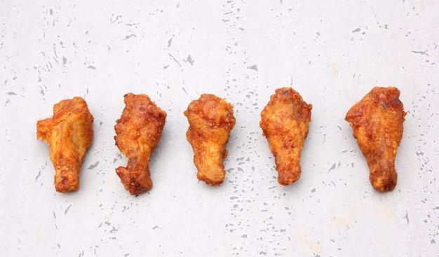 Alas de pollo frito coreano aisladas en un fondo gris en estudio.