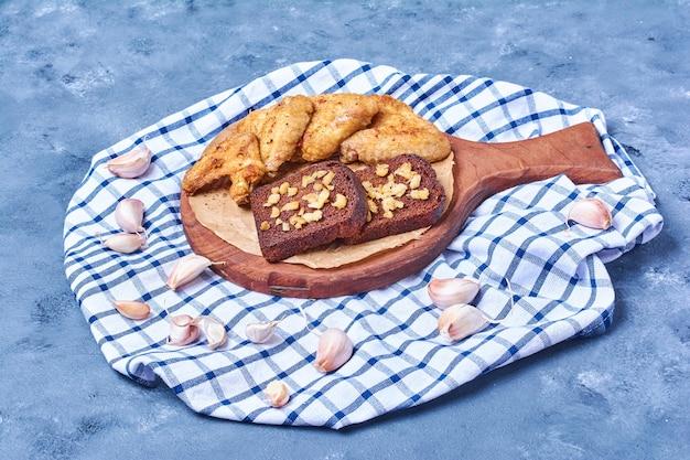 Alas de pollo frito con pan oscuro sobre una tabla de madera en azul
