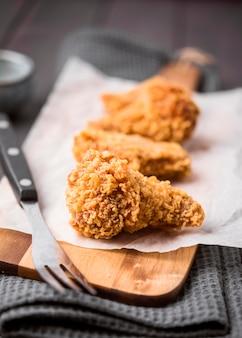 Alas de pollo frito de primer plano en la tabla de cortar con un tenedor