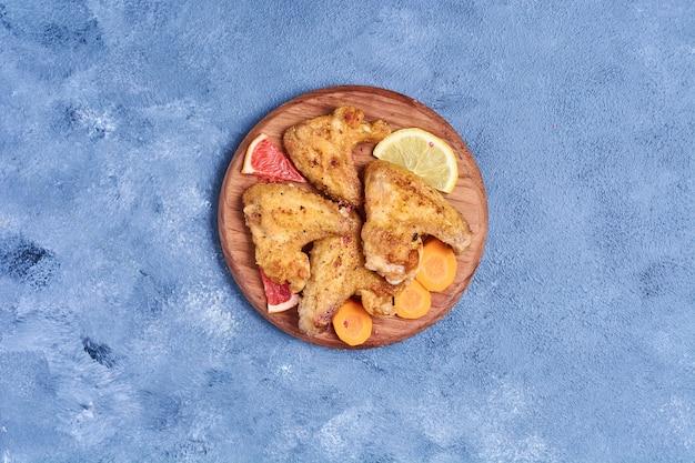 Alas de pollo frito en una tabla de madera en azul