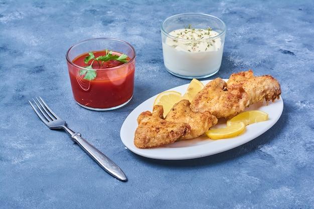 Alas de pollo con salsas en un plato blanco.