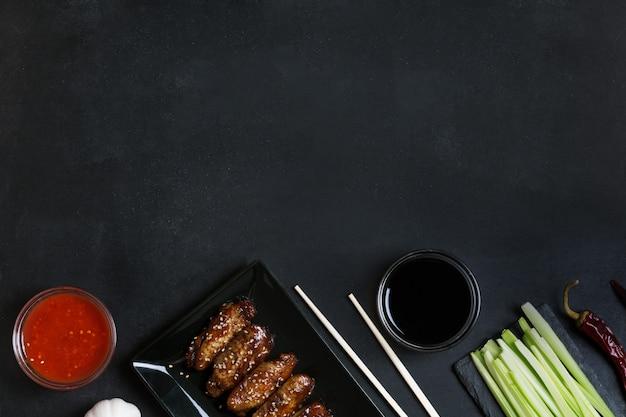 Alas de salteado asiáticas tradicionales con sésamo. ingredientes y palillos sobre la mesa