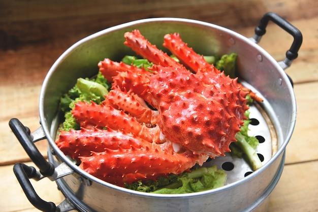 Alaska cangrejo real cocinó la comida del vapor en una olla al vapor mariscos y lechuga vegetales en la madera