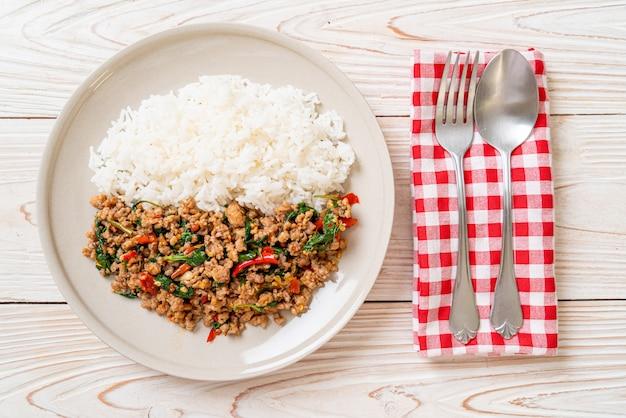 Albahaca tailandesa salteada con carne de cerdo picada sobre arroz cubierto