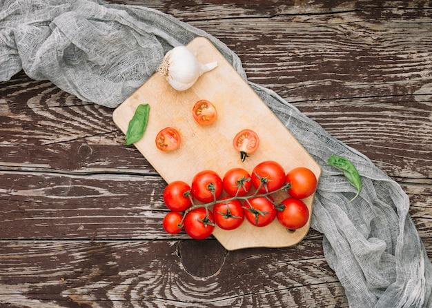 Albahaca; tomates cherry y dientes de ajo en una tabla de cortar con un paño gris sobre el fondo con textura de madera