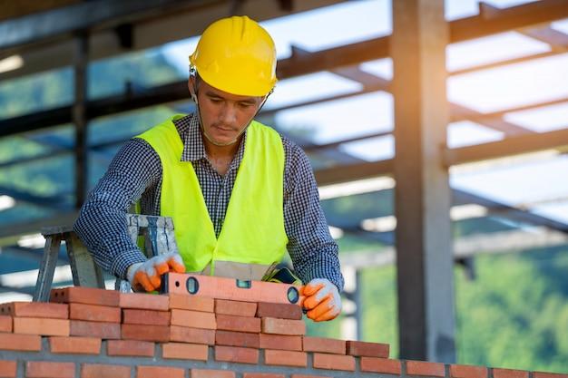 Albañil colocando ladrillos para hacer una pared en el sitio de construcción.