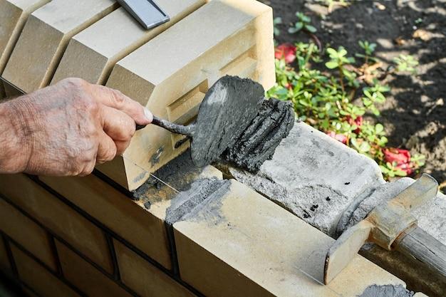 Albañil instalando ladrillos en la nueva cerca de ladrillos de revestimiento con espátula