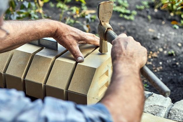 Albañil instalando ladrillos en la nueva cerca de ladrillos de revestimiento con un martillo