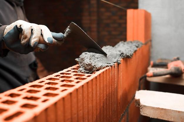 El albañil pone ladrillos para hacer una pared