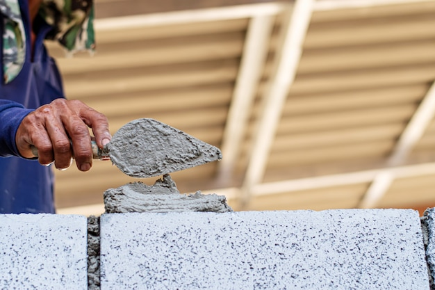 Albañil trabajador instalación de mampostería en la pared exterior.