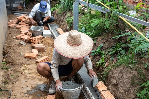 Albañilería trabajador de la construcción construyendo una pared de ladrillos.