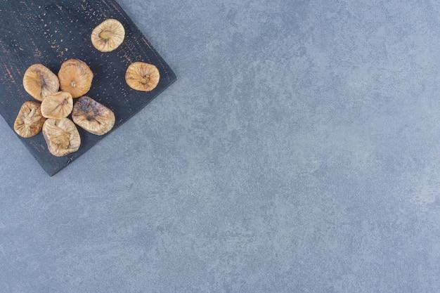 Albaricoque seco en el tablero, sobre el fondo de mármol.