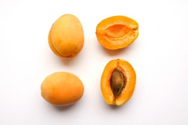Albaricoques aislados. fruta fresca de albaricoque entero con hoja y mitad aislado sobre fondo blanco con trazado de recorte