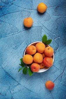 Albaricoques frescos dulces en el tazón blanco