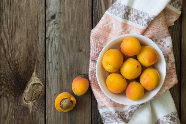 Albaricoques frescos en un recipiente sobre una mesa de madera sobre una toalla de cocina. copia espacio