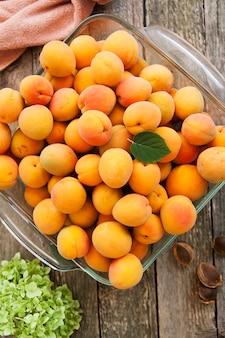 Albaricoques maduros con un recipiente de vidrio y semillas en una mesa de madera. frutas de verano, concepto de comida