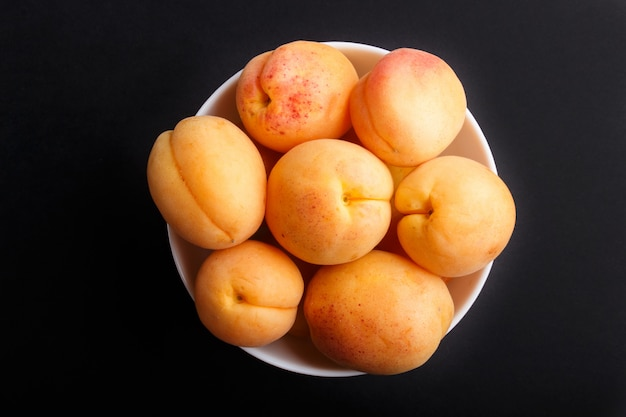 Albaricoques naranjas frescas en un tazón blanco sobre fondo negro