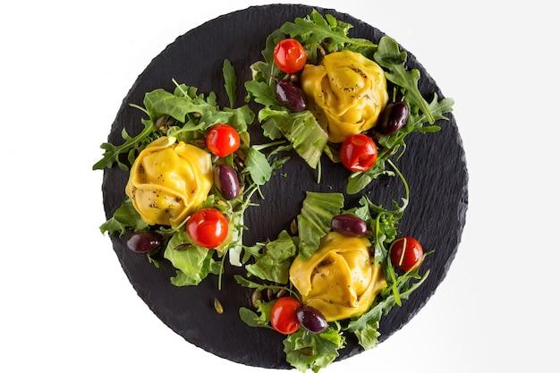 Albóndigas de carne al vapor manti con verduras y verduras en placa de piedra negra.