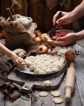 Albóndigas de carne cruda - pelmeni ruso en tabla de cortar e ingredientes