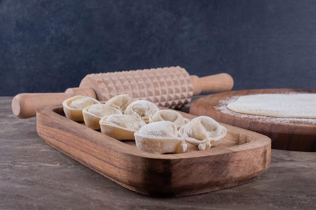 Albóndigas crudas sobre tabla de madera.