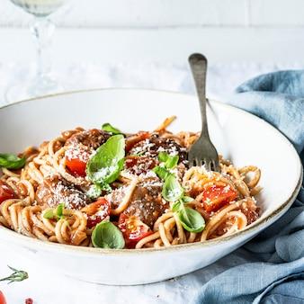 Albóndigas de espagueti con salsa de tomate marinara cubierta con parmesano y albahaca