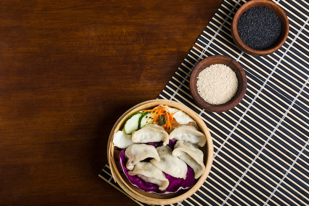 Albóndigas gyoza hervidas frescas dentro de los vapores calientes con semillas de sésamo blancas y negras en mesa de madera
