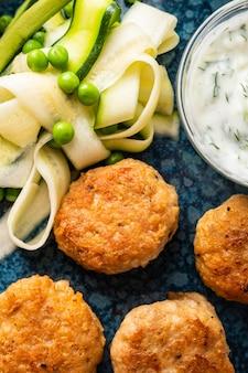 Albóndigas de pollo con ensalada de calabacín y guisantes, con salsa de yogur y ajo.