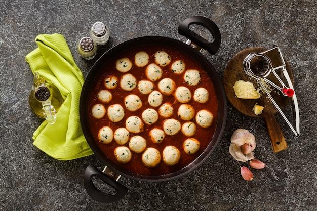 Albóndigas de queso y verduras con salsa de tomate en una sartén. cocina tradicional italiana para toda la familia, fiesta o menú de restaurante