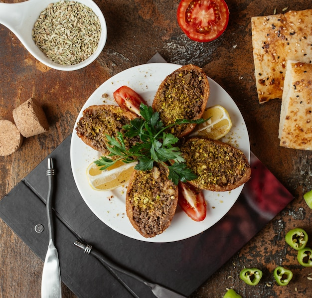 Albóndigas rellenas turcas ichli kofte servidas con limón, perejil y tomate