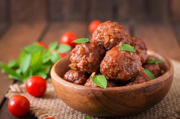 Albóndigas en salsa de tomate agridulce y albahaca en un tazón de madera