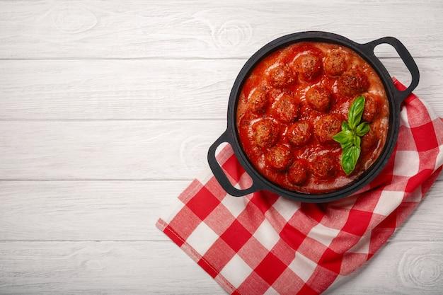 Albóndigas en salsa de tomate con especias y albahaca en una sartén sobre una tabla de madera blanca