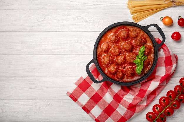 Albóndigas en salsa de tomate con especias y albahaca en una sartén y tomates cherry en una tabla de madera blanca