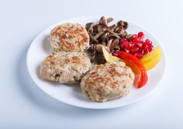 Albóndigas con setas de arroz, pimientos dulces y semillas de granada aisladas sobre fondo blanco.