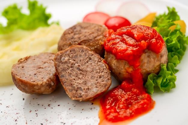 Albóndigas de ternera con arroz y salsa de tomate, sobre fondo de puré de patatas