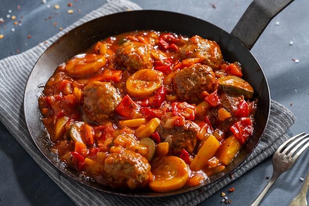 Albóndigas con verduras y salsa hecha en sartén y servida en la mesa.