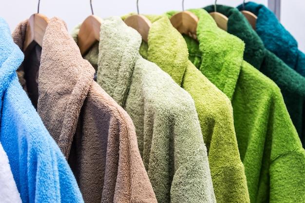 Albornoces de diferentes colores en la percha del baño.