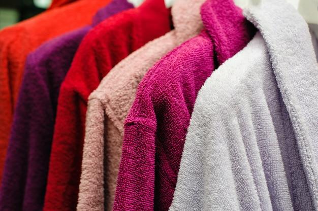 Albornoces de felpa de colores colgando en la tienda trempel