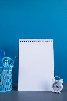Álbum de dibujo en blanco y papelería en mesa