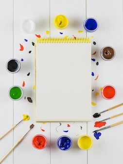 Un álbum de dibujo y frascos de pintura sobre una mesa de madera blanca. endecha plana.
