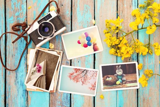 Álbum de fotos de cámara y papel retro en mesa de madera con flores