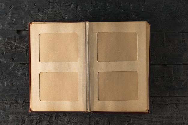 Álbum de fotos casero del vintage abierto en la tabla de madera oscura.