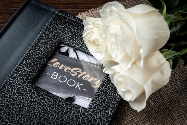Álbum de fotos gris y rosas blancas sobre la mesa de madera oscura.