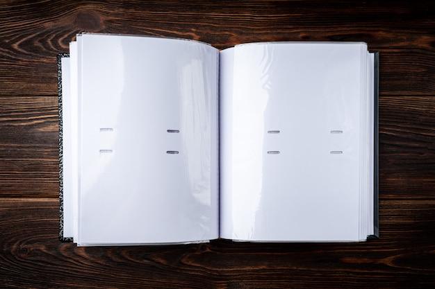 Álbum de fotos gris sobre mesa de madera oscura.