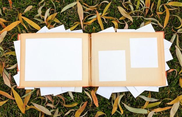 Álbum con viejas fotos familiares en el jardín sobre el césped con hojas de otoño. memorias del pasado.