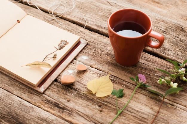 Álbum vintage con plantas de herbario y reloj de arena con una taza de té en la superficie de madera vieja