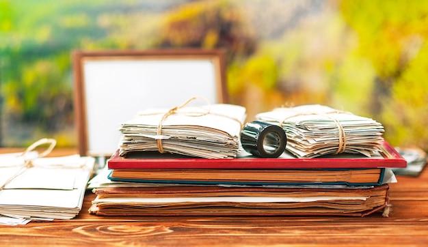 Álbumes de fotos antiguos con fotografías y películas sobre el fondo de la naturaleza en una mesa de madera marrón
